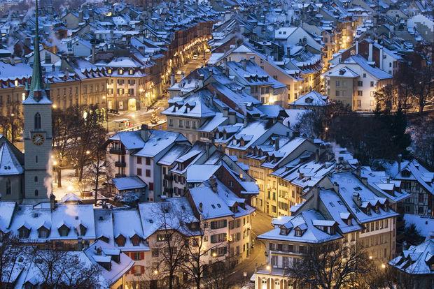 Bern, Switzerland at dusk after a snowfall. (AP photo by Peter Claunzer)